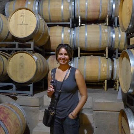Photo of Yvonne standing in front of wine barrels
